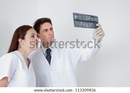 Dentist with dental nurse analyzing patient's X-ray report in clinic - stock photo