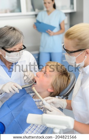 Dentist with nurse treatment on teenager patient at dental surgery - stock photo