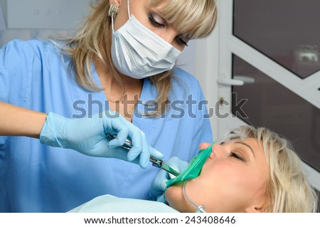 dentist with patient, installation of rubber dam - stock photo