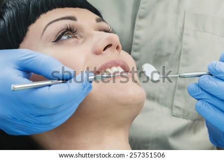 Dentist working on a perfect smile. Dentist makes the process of treatment of a beautiful young girl. - stock photo