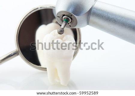 Dentistry. Wisdom tooth dental mirror and machine with drill - stock photo