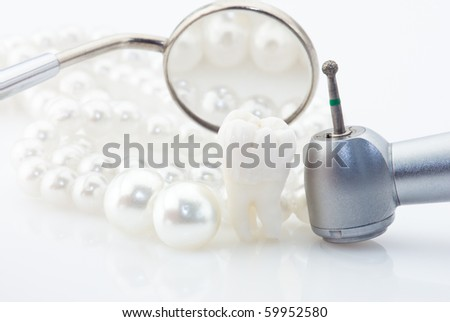 Dentistry. Wisdom tooth dental mirror, machine with drill and natural pearls - stock photo