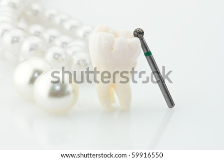 Dentistry. Wisdom tooth natural pearls and dental drill. - stock photo