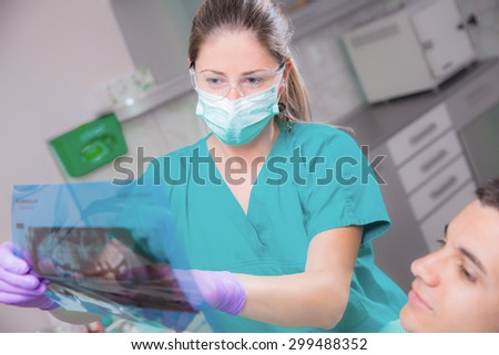 Dentistry Young woman dentist analyzes the dental X-ray image - stock photo