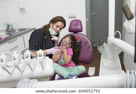 Dentists with a patient during a dental intervention to little girl