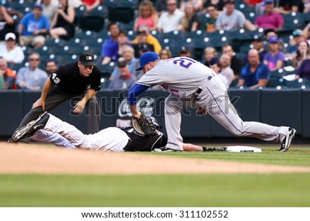 DENVER-AUG 21: New York Mets firstbaseman Lucas Duda tags out Colorado Rockies outfielder Charlie Blackmon during a game at Coors Field on August 21, 2015 in Denver, Colorado. - stock photo
