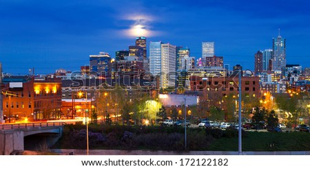 Denver, Colorado colorful panoramic skyline with full moon rising at dusk - stock photo