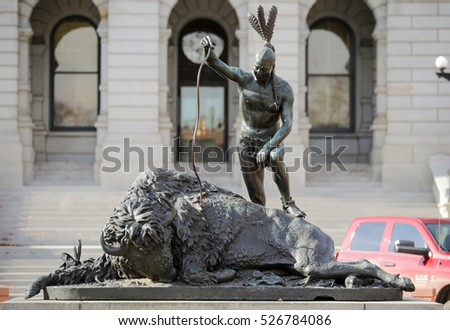 "Denver, Colorado - November 29, 2016: The statue ""The Closing of an Era"" at the Colorado capitol depicts an American Indian in triumph near a fallen bison"