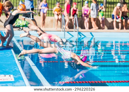 Denver, Colorado, USA-July 11, 2015. Kids swim meet in outdoor pool during the summer. - stock photo