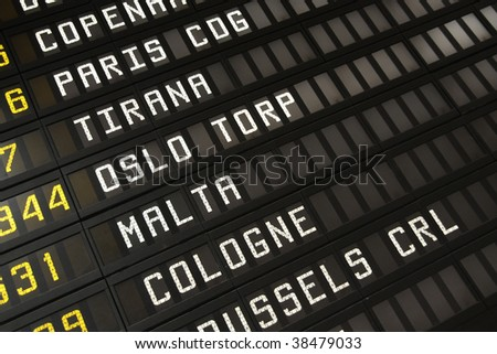 Departure board at an airport in Italy. Flights to Paris, Tirana, Oslo, Malta and Cologne. - stock photo