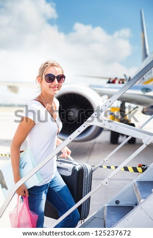 Departure - young woman at an airport about to board an aircraft on a sunny summer day