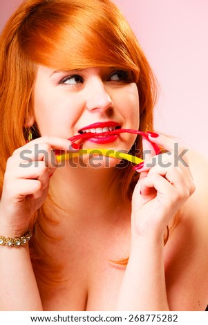Dependence on sweets. Young pretty red haired lying woman eat candy. Studio shot on pink background. - stock photo