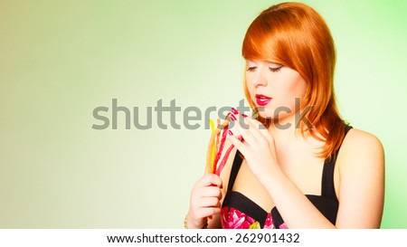 Dependence on sweets. Young red haired woman with candy on green background in studio. - stock photo