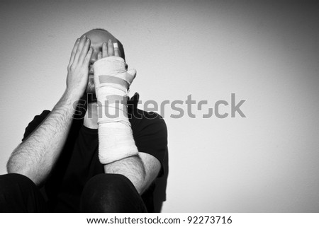 depressed adult man with injured hand - stock photo