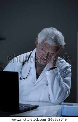 Depressed aged practitioner working in his office - stock photo