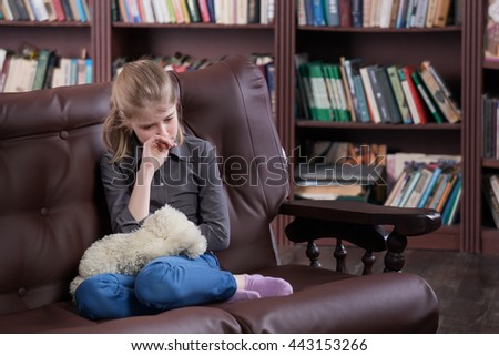Depressed alone crying girl sitting with toy at room - stock photo