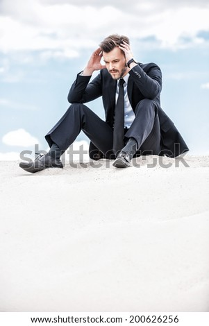 Depressed and confused businessman. Frustrated young businessman holding head in hands while sitting on the top of sand dune - stock photo