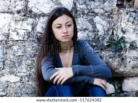 Depressed and lonely teenage girl, sad expression face, leaning on stone wall. - stock photo