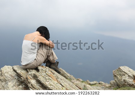 Depressed and sad woman alone in the mountain with a gray cloudy background - stock photo