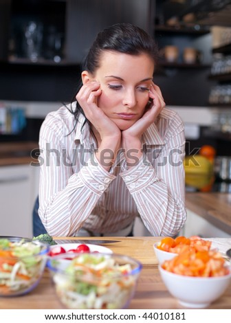 Depressed and sad woman in the kitchen - stock photo