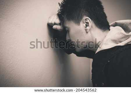 Depressed asian man with fist clenched leaning his head against a wall - stock photo