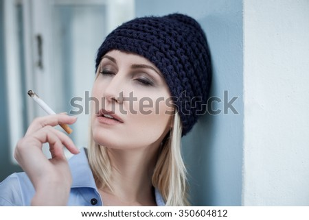 Depressed blond woman is smoking cigarette with enjoyment. She closed her eyes. The druggie is standing and leaning on the wall - stock photo