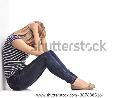 Depressed blond woman sitting on the floor with her head down and leaning against a wall isolated on white background - stock photo