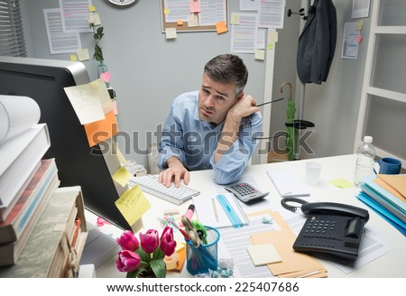 Depressed bored office worker at his desk holding glasses. - stock photo