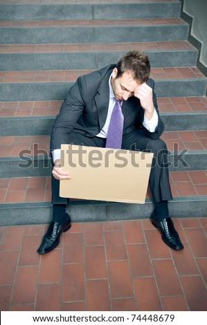 Depressed businessman holding blank cardboard - stock photo