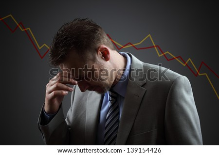 Depressed businessman in economic crisis with line graph showing negative trend - stock photo