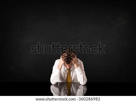 Depressed businessman sitting at a desk - stock photo