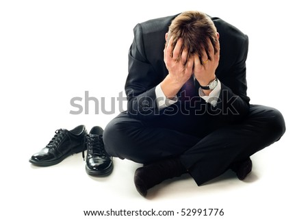 Depressed businessman sitting on the floor. Isolated on white background.