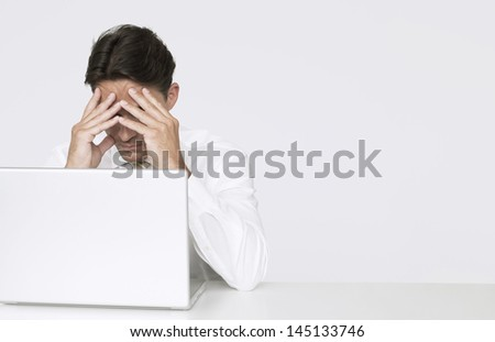 Depressed businessman with hands on face sitting with laptop at desk against white wall in office - stock photo
