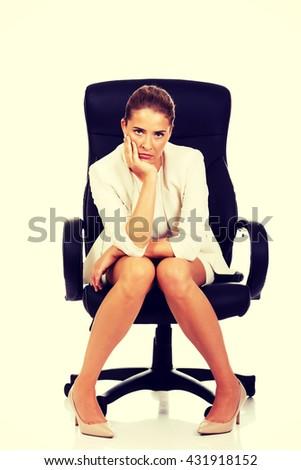 Depressed businesswoman sitting on armchair - stock photo