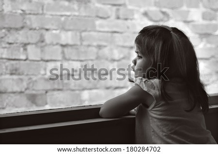Depressed child  (age 3-4) looks out of a window to a brick wall. concept photo - stock photo