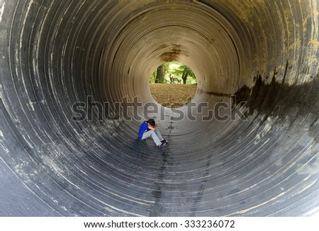 depressed child sitting in the large drainage pipe - stock photo