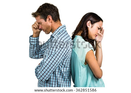 Depressed couple standing back to back against white background - stock photo