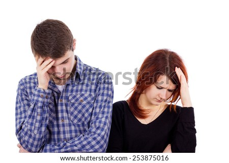 Depressed couple.Stressed couple. Depressed young couple standing close to each other holding hand to head while isolated on white - stock photo