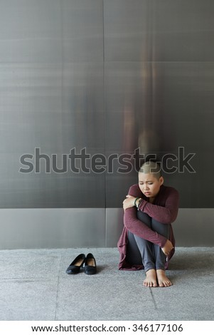 Depressed crying woman sitting on the floor - stock photo