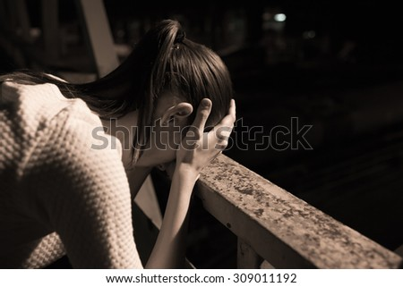 Depressed girl in a night time setting.  - stock photo