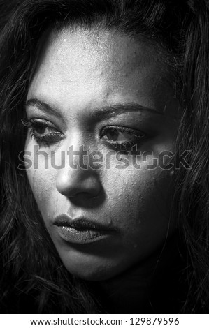 Depressed girl in tears with bad make-up concept in monochrome