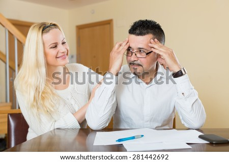 Depressed husband calculating the invoices, wife reassuring him   - stock photo