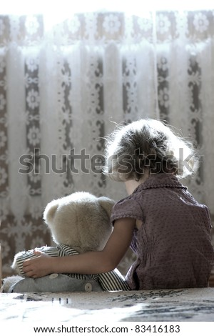 Depressed little girl hugging teddy bear - stock photo