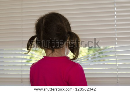 Depressed, lonely and abused little girl looks outside through window. - stock photo