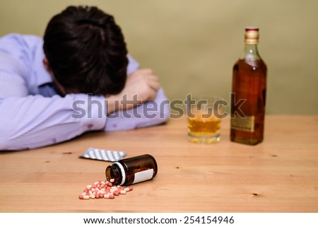 depressed man drinking alcohol and taking pills - stock photo - stock photo