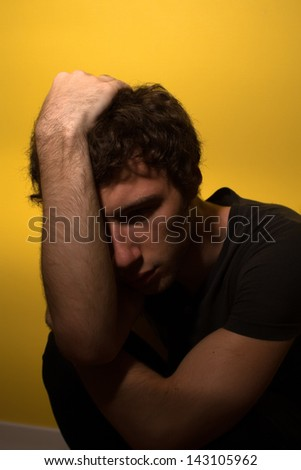 Depressed man embracing his head - stock photo