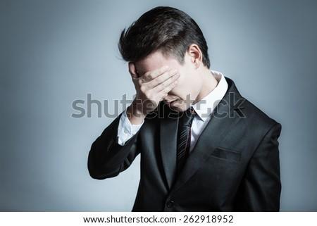 Depressed man in suit - stock photo
