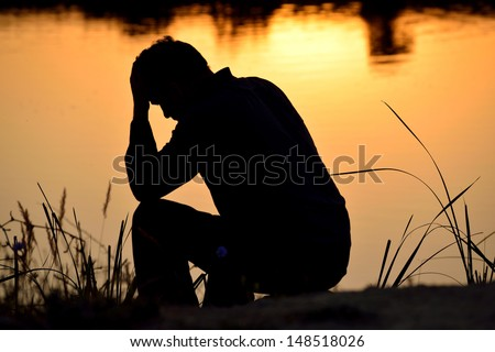 depressed man sitting against the light reflected in the water - stock photo