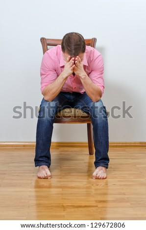 Depressed man sitting on a chair against the wall - stock photo