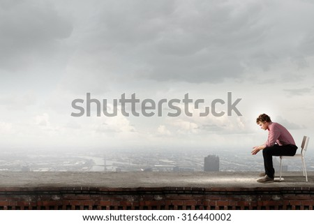 Depressed man sitting on a chair all alone - stock photo